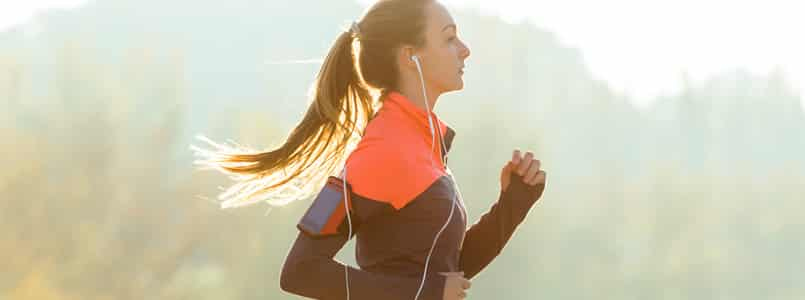 Woman running outdoors to boost metabolism for weight loss