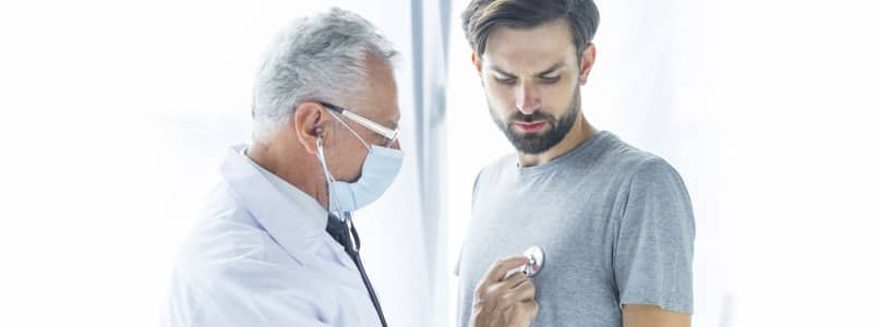 doctor listening to young man's heart