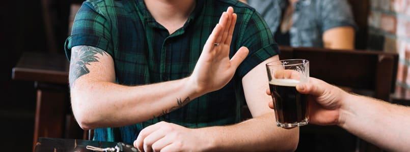 man rejecting beer
