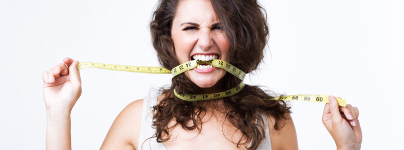Frustrated woman biting on measuring tape