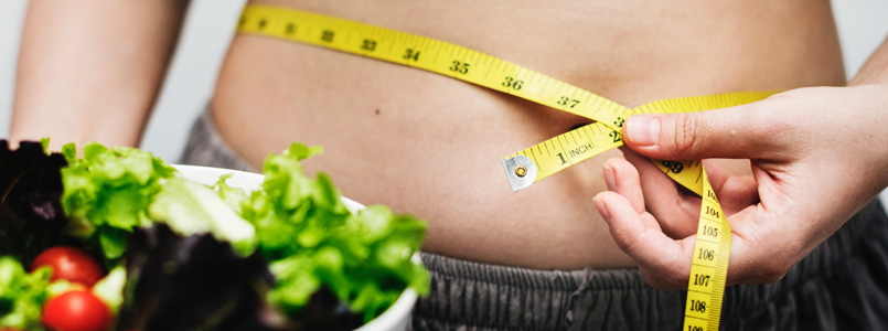person measuring waist and holding a green salad