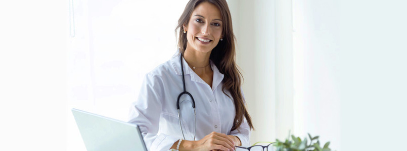 young, female doctor smiling from behind a desk