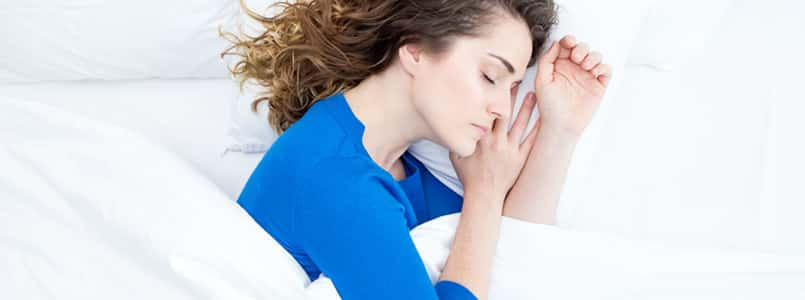 Woman sleeping restfully in her bed after taking melatonin