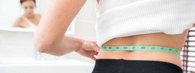 thin woman measuring waist