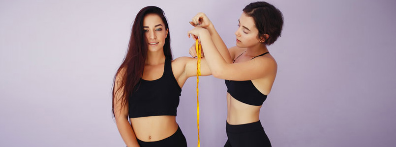 two women: one measuring the other's upper arm circumference