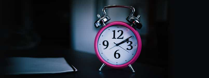 pink alarm clock in dark room