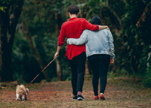 couple walking outdoors with their dog