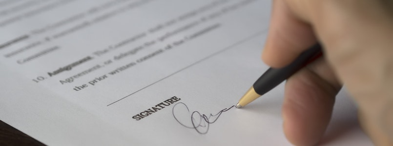hand holding pen and signing document